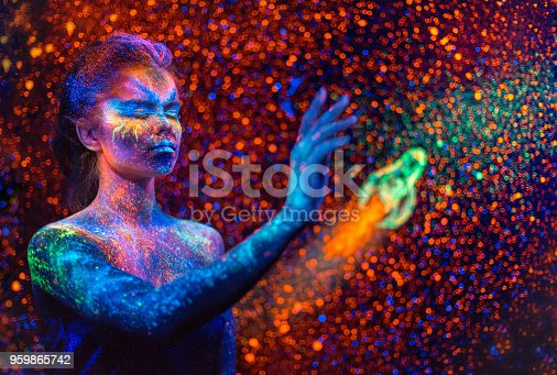 Beautiful teenage girl is posing on luminous starry sky  background with rocket. Eccentric fluorescent (neon, luminescent) painting on a face (the makeup) and on a body (the body art). Studio shooting in ultraviolet lighting