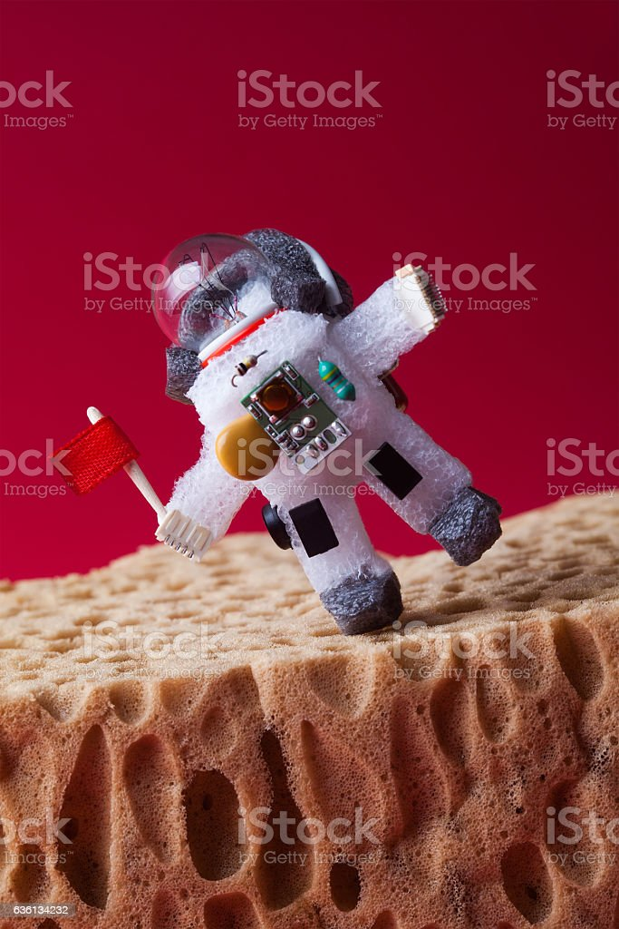 Spaceman explores Mars. Light bulb toy dressed in spacesuit and stock photo