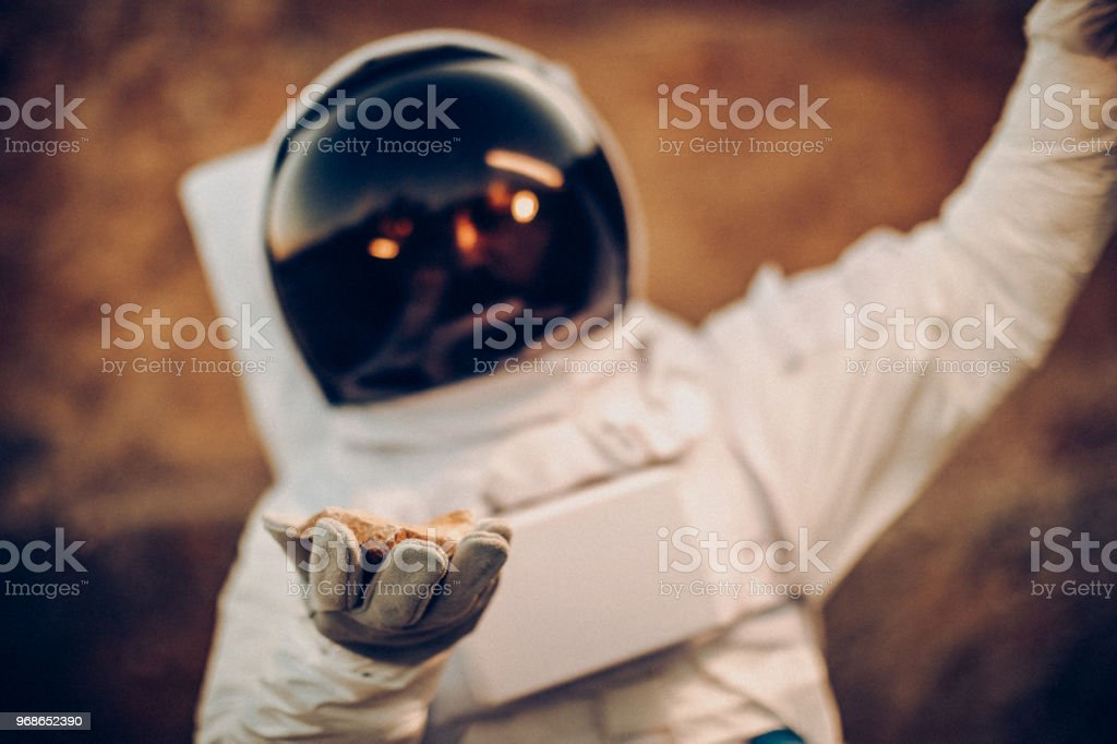 Spaceman holding rock-object from the moon, celebrating big discovery