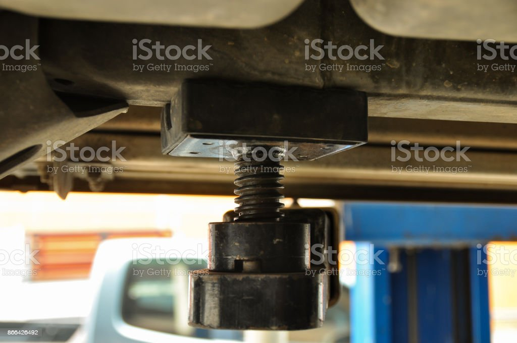 Spacer and spiral support under the car stock photo