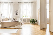 Spacious and bright bedroom interior with beige decorations, hardwood floor and a book on the window sill seat
