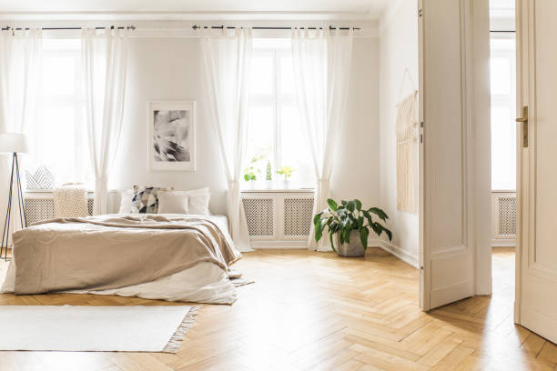 Spacious and bright bedroom interior with beige decorations, hardwood floor and a book on the window sill seat Spacious and bright bedroom interior with beige decorations, hardwood floor and a book on the window sill seat bedroom stock pictures, royalty-free photos & images