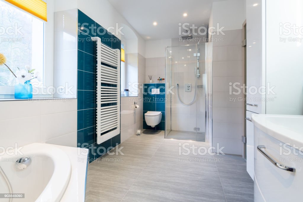 Spacious bathroom in blue and white tones with heated floors, walk-in shower, sink vanity and skylights stock photo