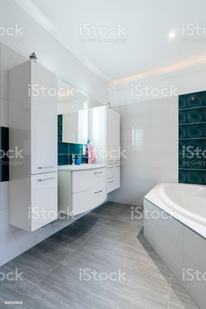 Spacious bathroom in blue and white tones with heated floors, walk-in shower, sink vanity and skylights Vertical Shot stock photo