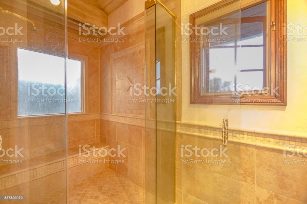 Spacious bathroom in gray tones with heated floors and walk-in shower stock photo