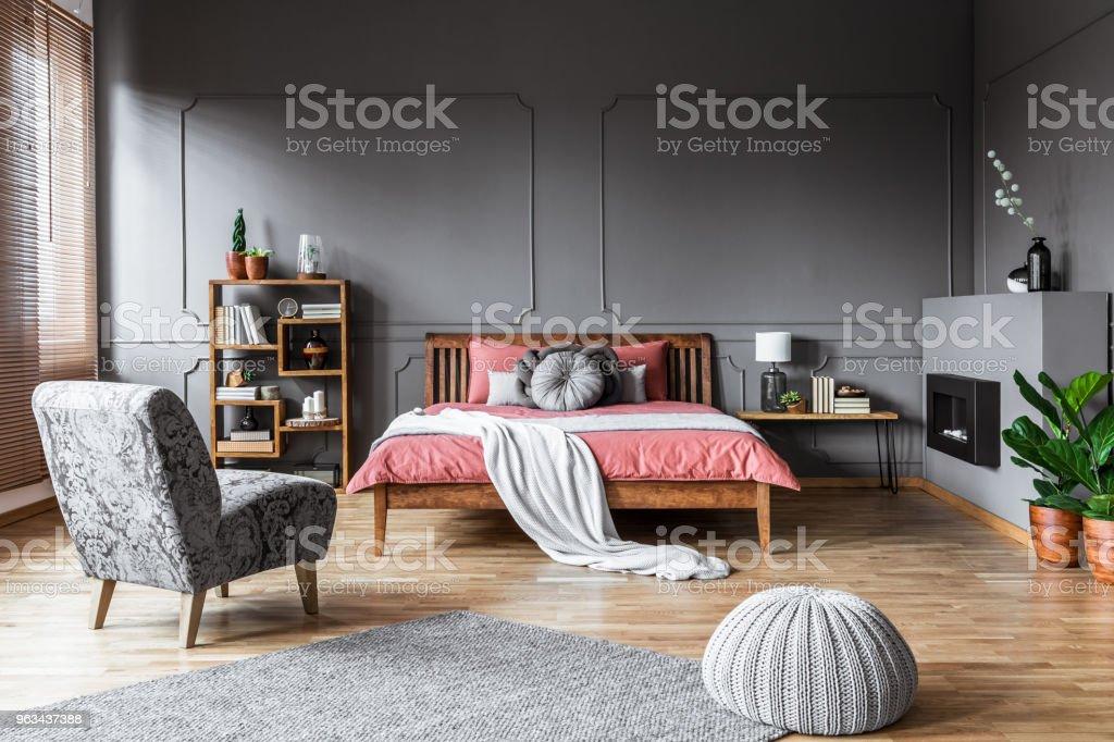 Geraumiges Schlafzimmer Einrichtung Mit Hocker Und Grau Sessel Vor Einem Rosa Bett Mit Holzernen Bedhead Echtes Foto Stockfoto Und Mehr Bilder Von Bett Istock