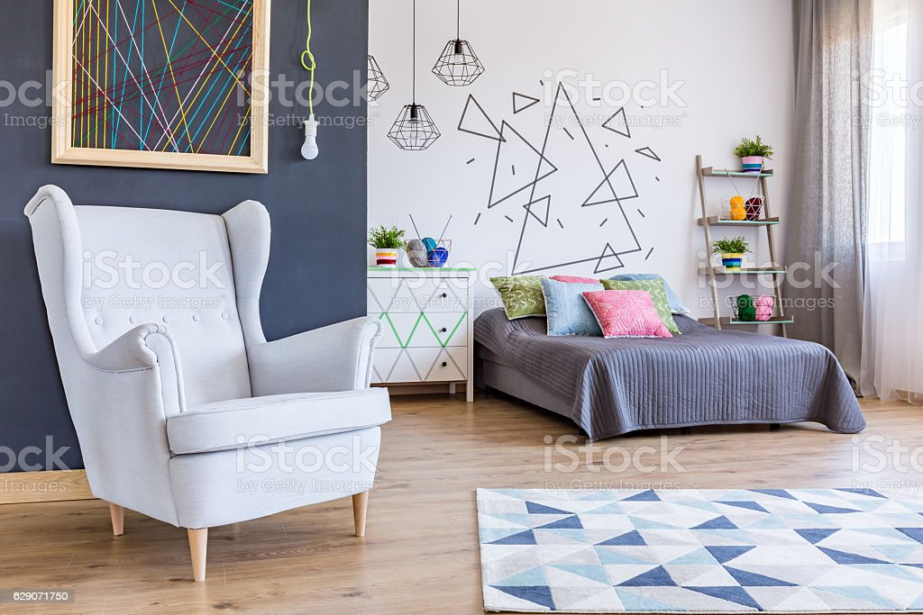Spacious bedroom with cosy armchai stock photo