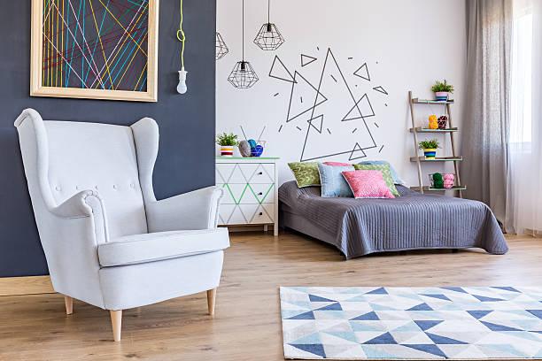 spacious bedroom with cosy armchai - teppich geometrisch stock-fotos und bilder