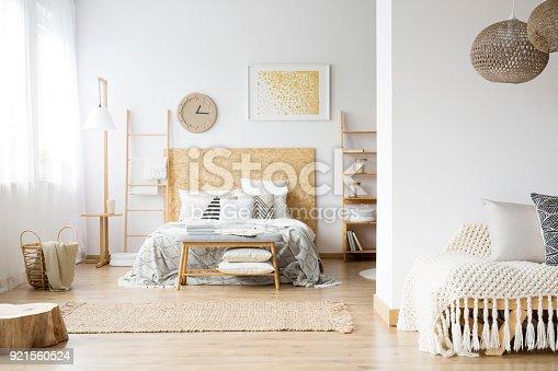 istock Spacious bohemian bedroom with wood 921560524