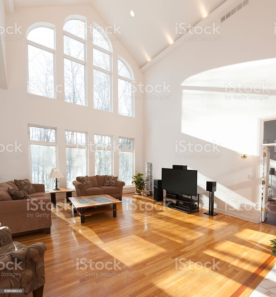 Spacious bright family room with cathedral ceiling and window wall stock photo