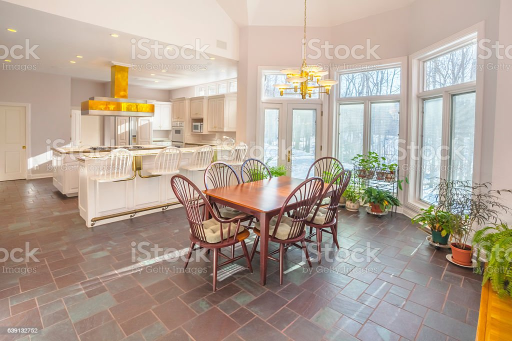 Spacious casual dining area adjoining modern white kitchen stock photo