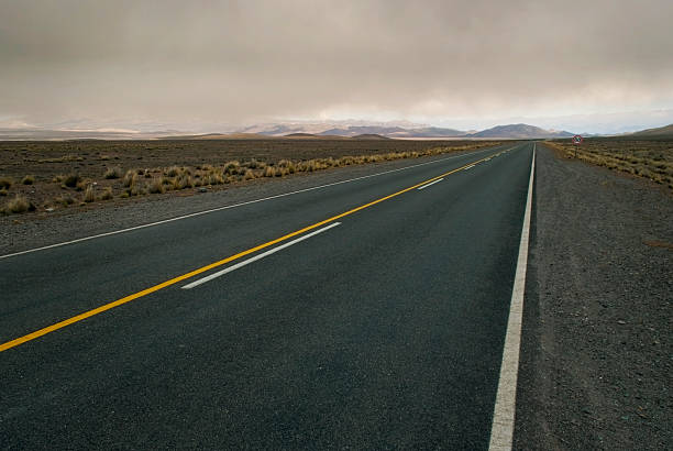 Spacious cloudy landscape crossed by empty road​​​ foto