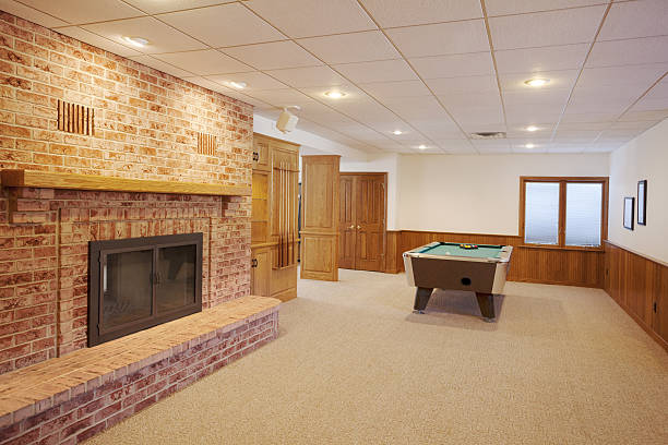 Spacious finished basement with pool table and fireplace Spacious finished basement with pool table, fireplace, custom lighting. man cave stock pictures, royalty-free photos & images