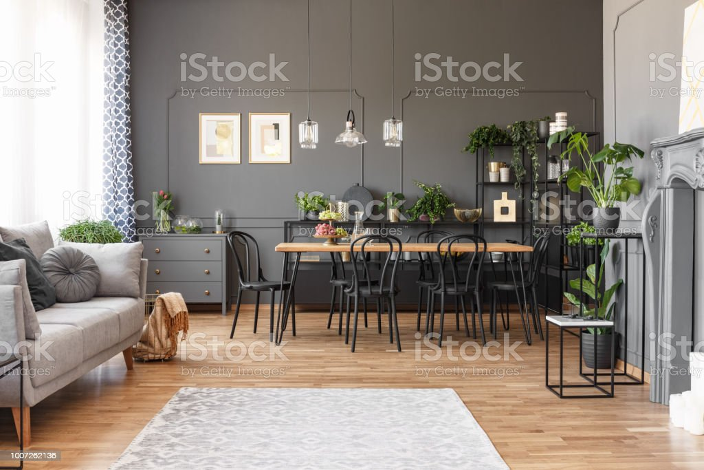 Spacious flat interior with gray sofa, wooden dining table, black chairs and a rug on a wooden floor. Real photo stock photo