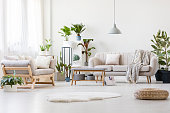 Pouf and white fur in spacious floral living room interior with wooden bench, beige sofas and plants