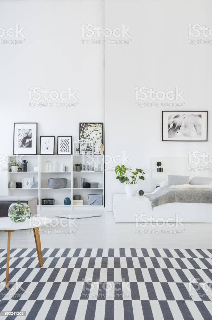 Spacious, gray and white bedroom interior with a striped rug, bookcases with decorations and a botanic poster above the bed. Real photo stock photo