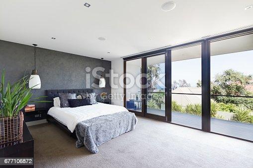 istock Spacious interior of designer master bedroom in luxury Australian home 677106872