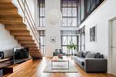 istock Spacious living room with wooden stairs 1213241044