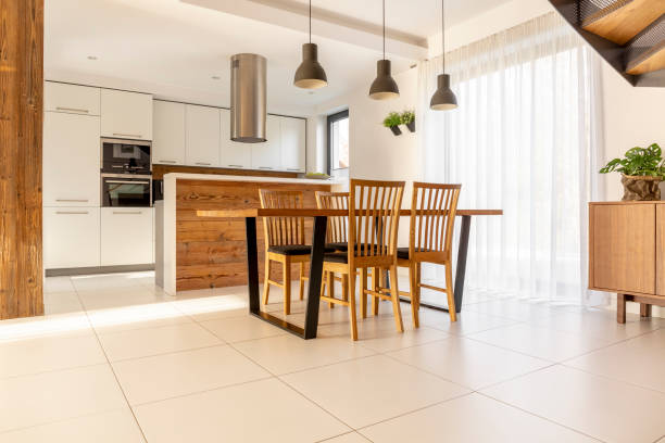 Spacious, open kitchen and dining room with wooden table and chairs, large window, white cupboards and tiles on the floor. Real photo stock photo