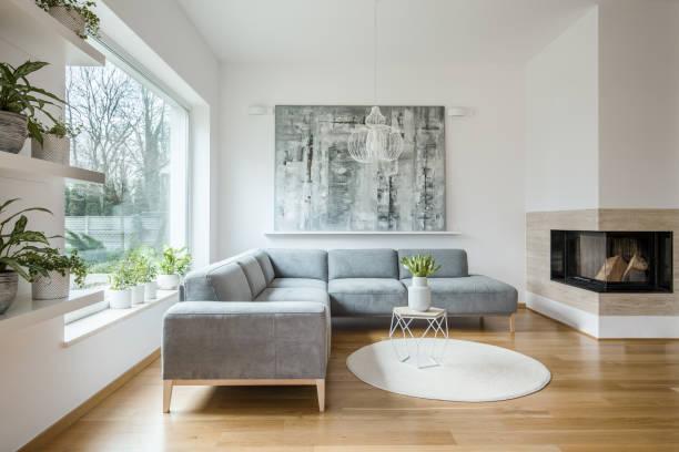 weiße wohnzimmer interieur mit grauen ecke sofa, große moderne kunst malerei und kamin - große wohnzimmer stock-fotos und bilder