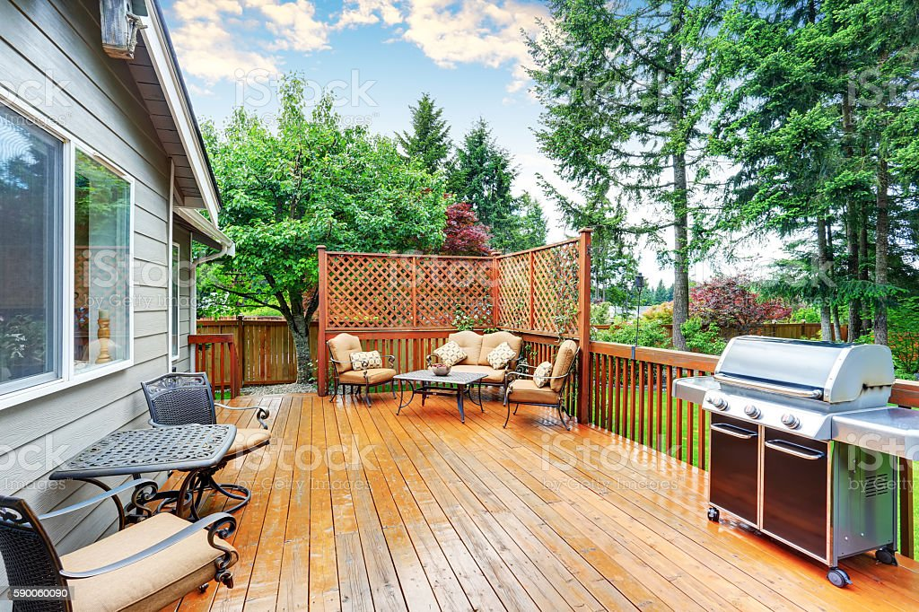 Spacious wooden deck with patio area and attached pergola. stock photo