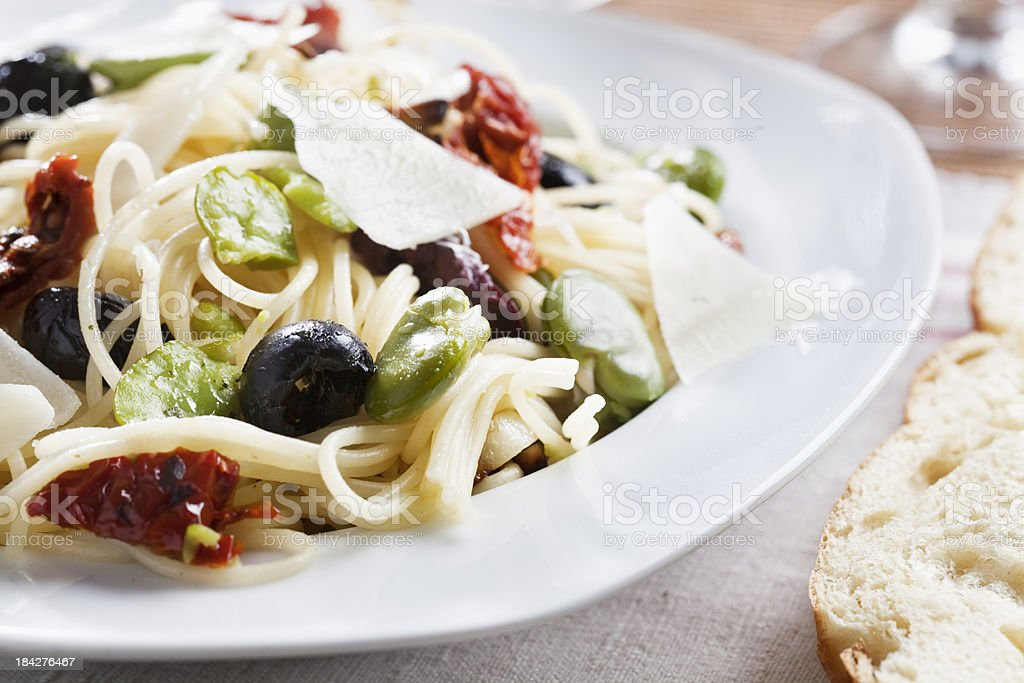 spagetthi with fava beans, olives and dried tomatoe royalty-free stock photo