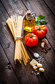 Vertical shot of spaghetti with ingredients for cooking pasta composition on rustic wooden table. The composition includes spaghetti, olive oil, garlic cloves, peppercorns, salt, tomatoes, oregano, basil and Parmesan cheese. Predominant colors are brown and yellow. Low key DSRL studio photo taken with Canon EOS 5D Mk II and Canon EF 100mm f/2.8L Macro IS USM