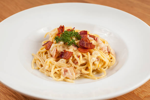 spaghetti alla cabonara in der tiefen runde platte - pasta cabonara stock-fotos und bilder