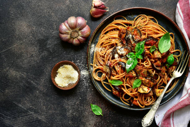 Spaghetti alla norma - traditional italian pasta Spaghetti alla norma - traditional italian pasta with eggplants and tomato on a plate over dark slate, stone or concrete background. Top view. whole wheat stock pictures, royalty-free photos & images