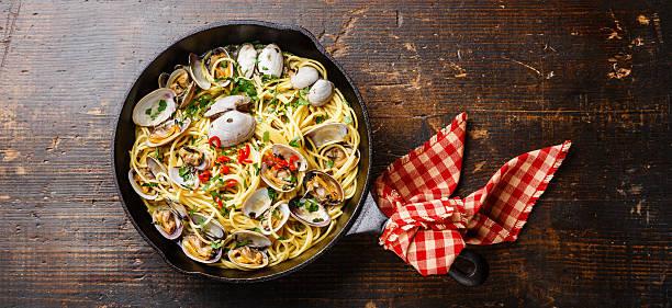 spaghetti alle vongole on iron pan - pasta vongole bildbanksfoton och bilder