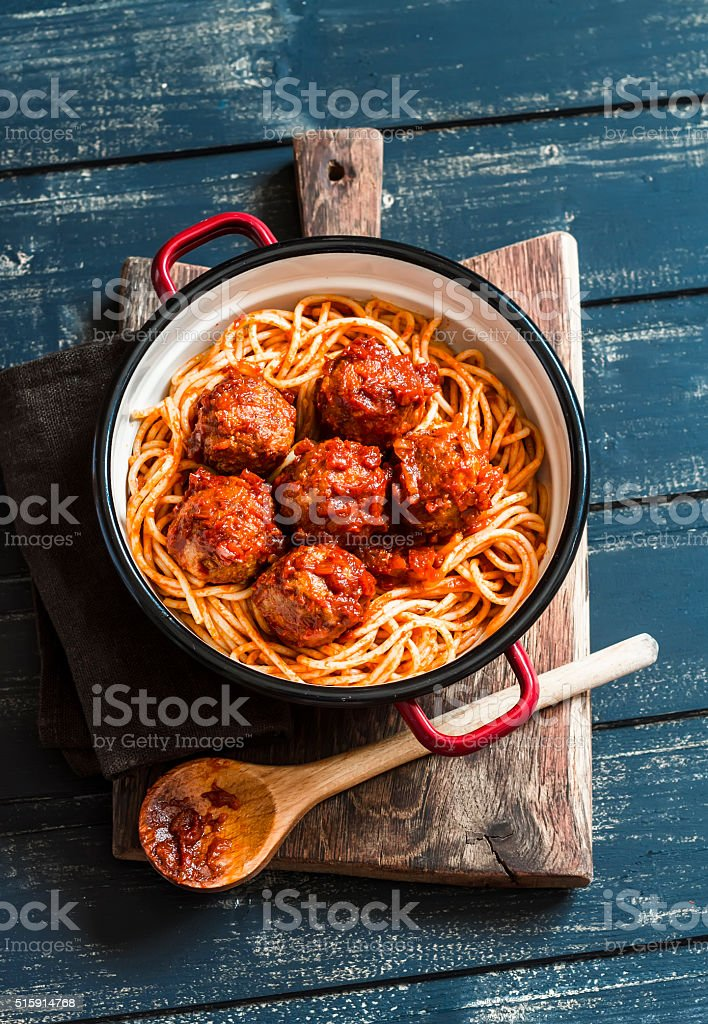 Spaghetti and meatballs in tomato sauce on wooden rustic board. stock photo