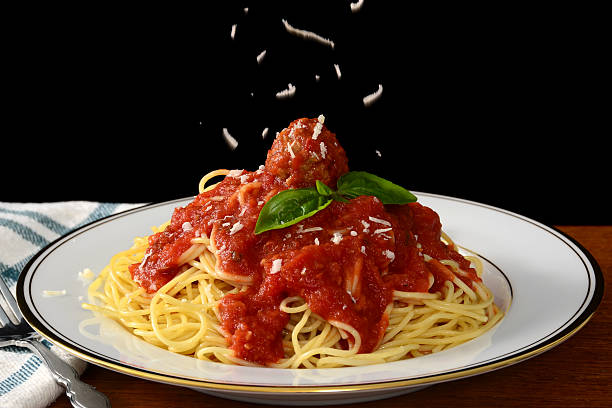Spaghetti and Meatballs Freshly grated parmesan cheese falls on a plate of spaghetti and meatballs. spaghetti stock pictures, royalty-free photos & images