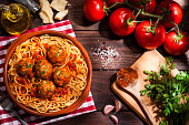 Top view of a plate filled with spaghetti and meatballs with some ingredients for preparation like tomatoes, parsley, garlic, olive oil and Parmesan cheese shot on rustic wooden table. Low key DSRL studio photo taken with Canon EOS 5D Mk II and Canon EF 100mm f/2.8L Macro IS USM