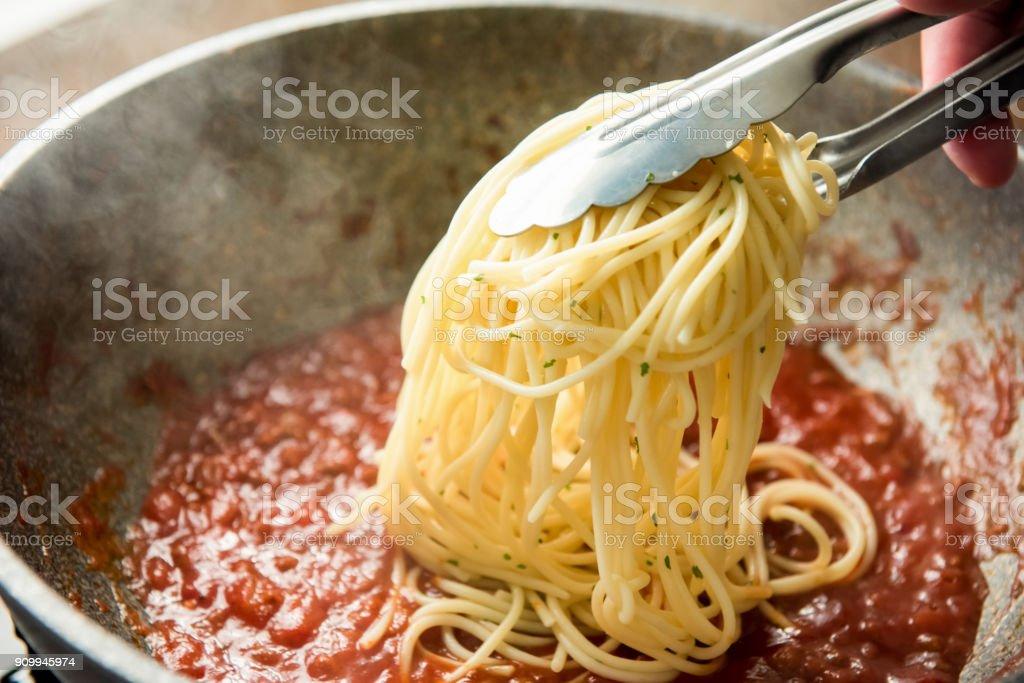 Spaghetti in die Pfanne mit heißem Bolognese-Sauce gestellt wird – Foto