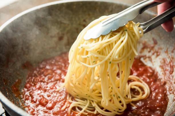 뜨거운 bolognese 소스 냄비에 넣어 스파게티 되 - 스파게티 뉴스 사진 이미지
