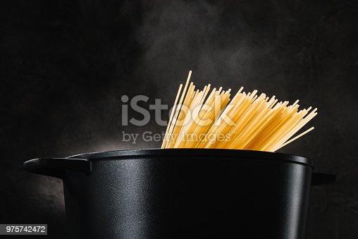 spaghetti boiling in black pan on dark background
