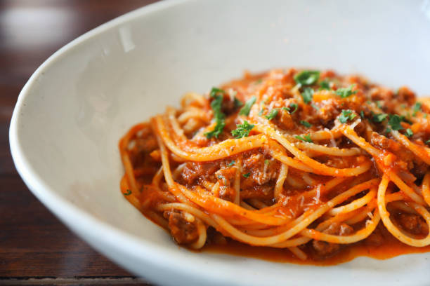 spaghetti Bolognese with minced beef and tomato sauce garnished with parmesan cheese and basil , Italian food spaghetti Bolognese with minced beef and tomato sauce garnished with parmesan cheese and basil , Italian food spaghetti stock pictures, royalty-free photos & images