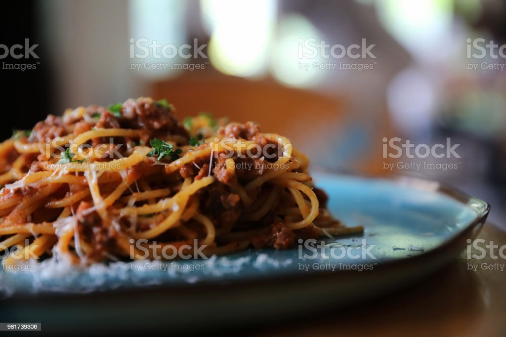 spaghetti Bolognese with minced beef and tomato sauce garnished with parmesan cheese and basil , Italian food stock photo