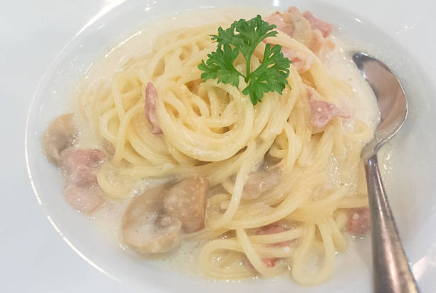 spaghetti cabonara inside white dish - pasta cabonara stock-fotos und bilder