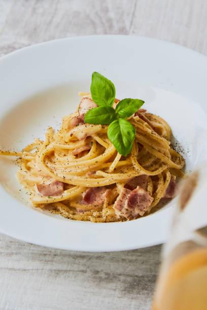 spaghetti carbonara on white palte with basil leaf stock photo