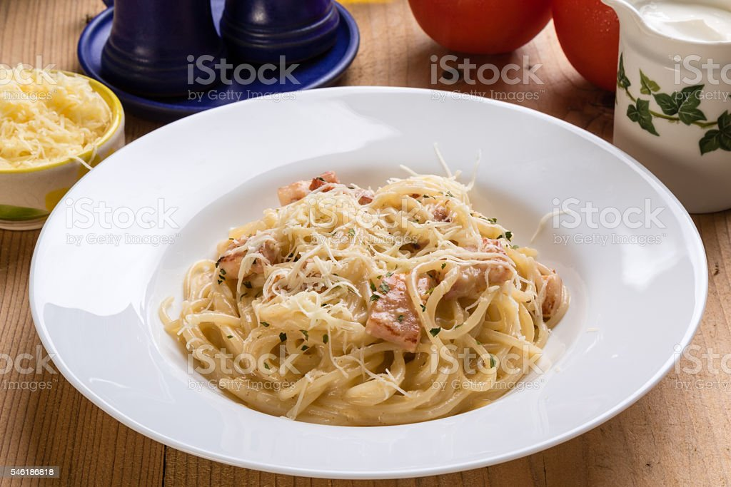 spaghetti carbonara on wooden table stock photo