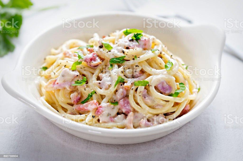 Spaghetti carbonara with bacon and fresh parsley stock photo