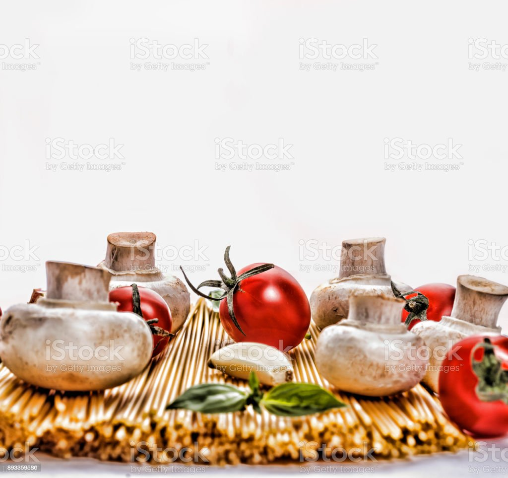 Spaghetti. Conception: National Spaghetti Day in the USA. 4 January. Raw spaghetti with various ingredients, cherry tomatoes, mushrooms, garlic. Isolated on white background stock photo