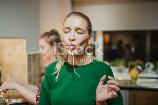 Young woman is posing for the camera with spaghetti hanging out her mouth.