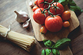 Spaghetti, garlic, basil and tomatoes on a cutting board. Raw food.