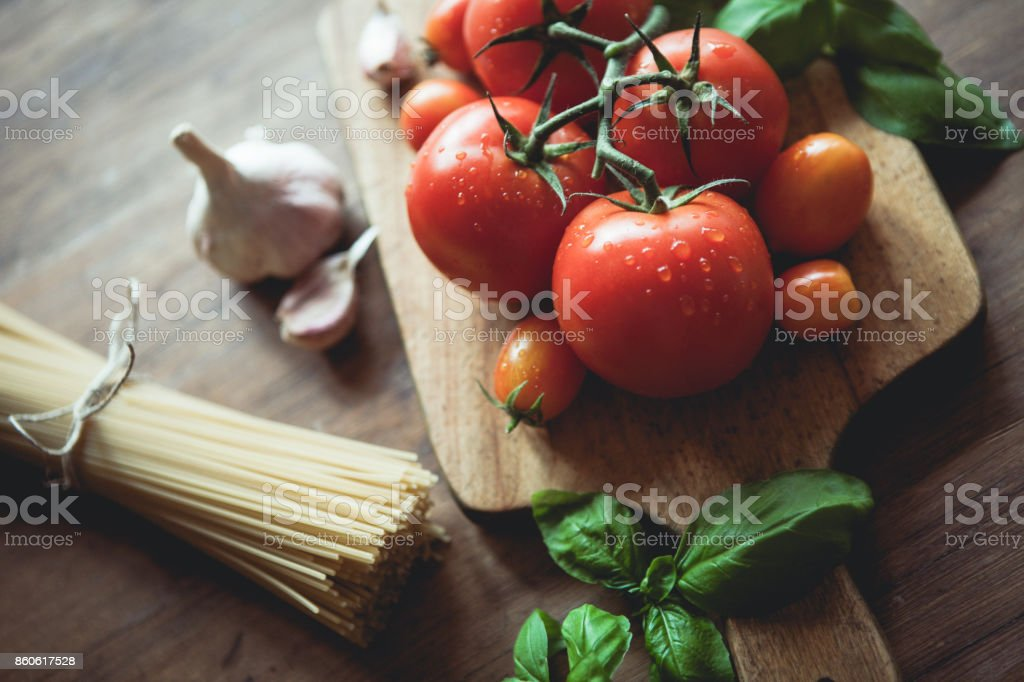 Spaghetti, garlic, basil and tomatoes on a cutting board stock photo