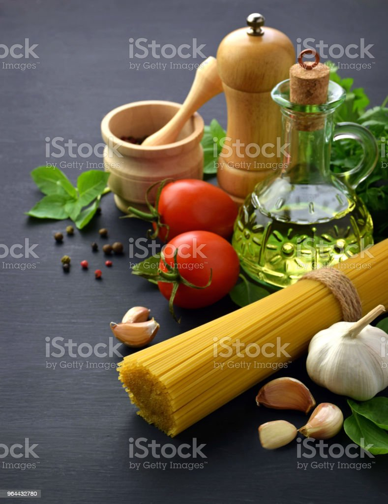 Spaghetti, garlic, basil, parsley, cilantro, olive oil, pepper, spices and cooking utensils on a dark background. Close-up. Kitchen background. Concept. - Royalty-free Abundance Stock Photo
