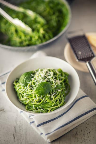 spaghetti. grüne spaghetti mit spinat und parmesan. italienische und mediterrane küche - spaghetti mit spinat stock-fotos und bilder
