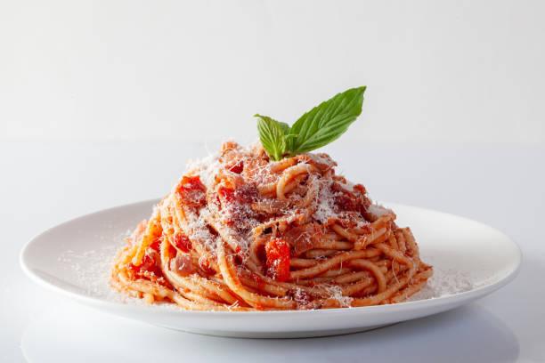 spaghetti in a dish on a white background - macarrão imagens e fotografias de stock