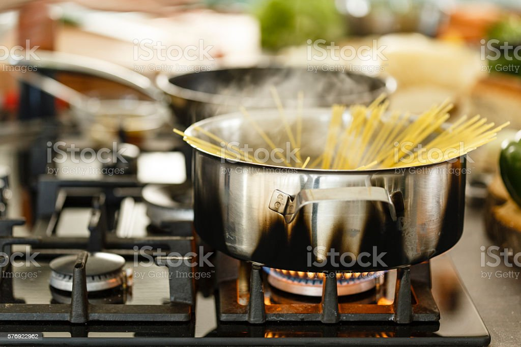 Spaghetti in boiling water on gas stove stock photo